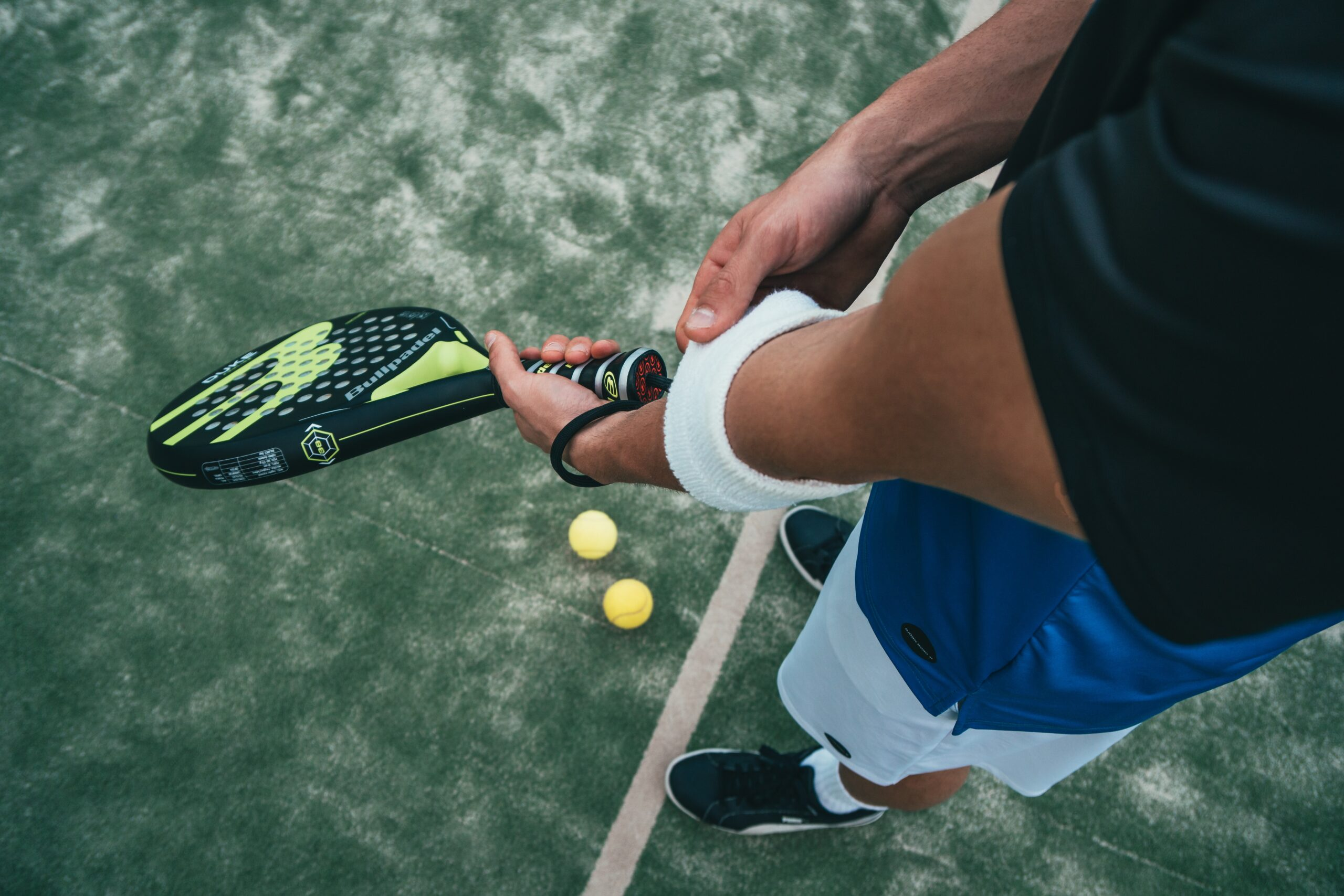 Person Holding Black and Green Tennis Racket